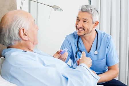 Happy Caretaker Discussing Prescription With Senior Man Stock Photo