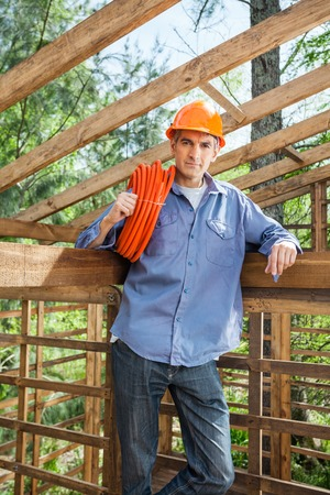 Confident Construction Worker Holding Pipe In Timber Cabin photo