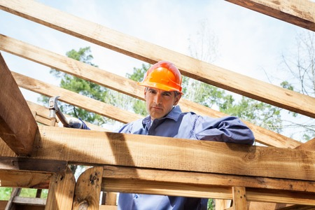 hammering: Confident Construction Worker Hammering Nail On Timber Frame