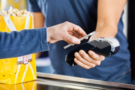 technology transaction: Man Making Payment Through NFC Technology At Cinema Stock Photo