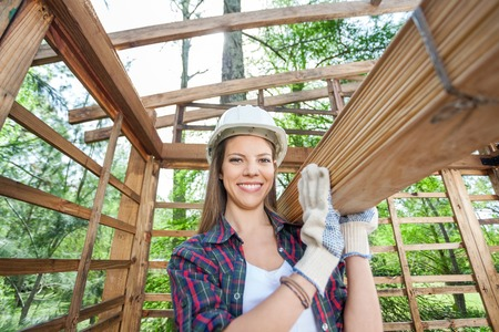 Happy Female Worker Carrying Wooden Planks