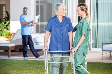 enfermera: Enfermera asiste a la mujer mayor a recorrer con el capítulo Zimmer Foto de archivo