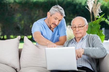 Nurse Erklären etwas auf Laptop zu alter Mann