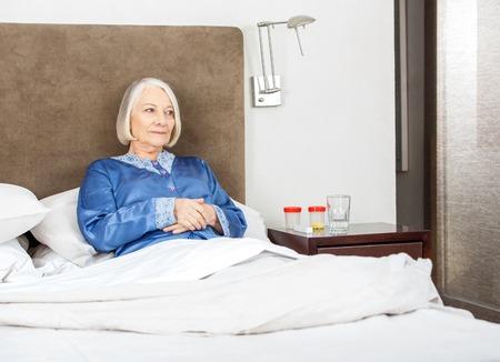 Donna anziana rilassante sul letto photo