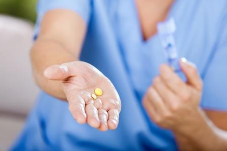 caretaker: Midsection Of Male Caretaker Giving Medicine