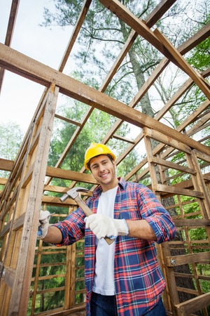 hammering: Smiling Construction Worker Hammering In Timber Cabin