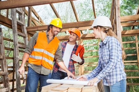 Happy Workers Discussing Over Blueprint At Site