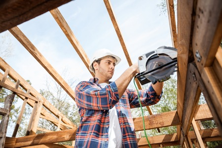 timber: Construction Worker Using Electric Saw On Timber Frame At Site Stock Photo