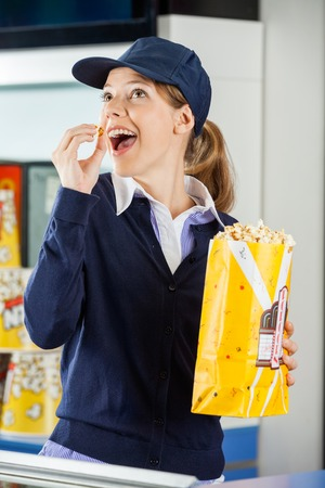 concession: Happy Worker Eating Popcorn At Cinema Concession Stand Stock Photo