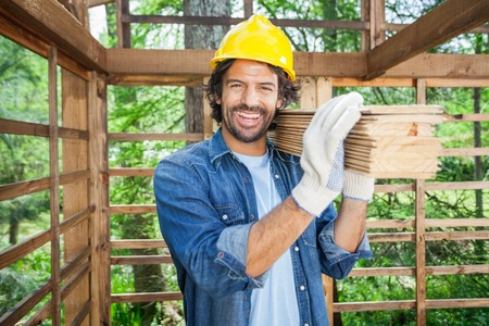 Happy Worker Carrying Wooden Planks On Shoulder photo