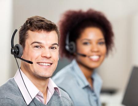 Rappresentante del servizio clienti con il collega di lavoro in ufficio photo