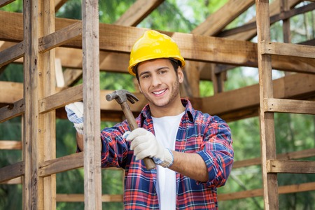 Happy Construction Worker Holding Hammer At Site photo