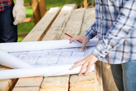 female architect: Midsection of female architect with blueprint at site Stock Photo