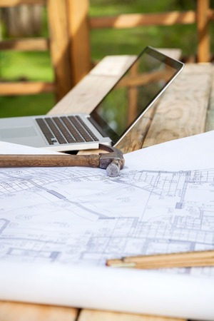 Hammer and blueprint with laptop on stacked wooden planks at construction site