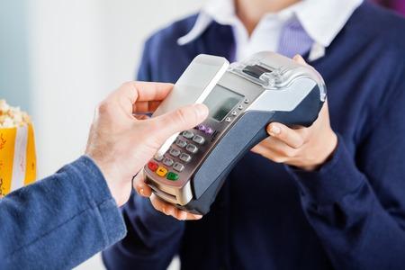 tarjeta de credito: Recorta la imagen de hombre que usa la tecnología NFC para pagar la factura en el cine