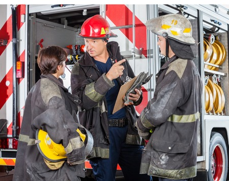 fire fighter: Mature male firefighter discussing with colleagues against truck at fire station Stock Photo