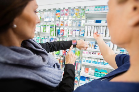 mid adult   female: Mid adult female customer showing smartwatch to pharmacist in drugstore