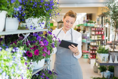 Beautiful mid adult florist using digital tablet while standing by trolley in flower shop