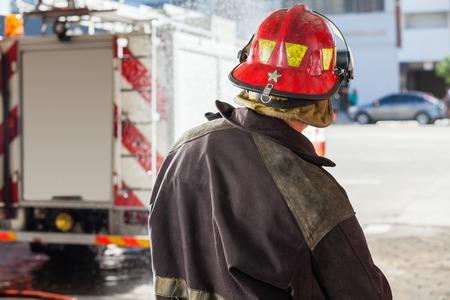 bombera: Vista trasera del bombero pulverización de agua masculina en la estación de bomberos