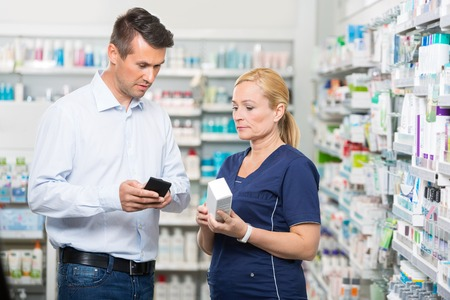 product information: Mid adult male customer showing product information on mobile phone to pharmacist in pharmacy Stock Photo