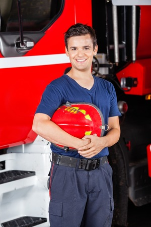 firetruck: Portrait of happy male firefighter holding helmet while standing against firetruck at station