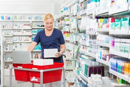 updating: Mature female chemist updating stock in laptop at pharmacy Stock Photo