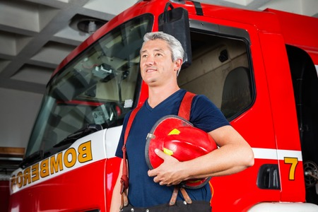 firetruck: Smiling mature fireman looking away while holding red helmet against firetruck at station