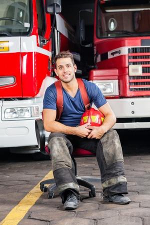 fireman helmet: Full length portrait of smiling firefighter holding helmet while sitting against trucks at fire station