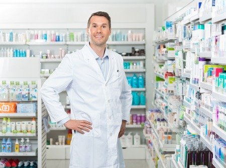 mid adult male: Portrait of confident mid adult male pharmacist standing with hands on hip in pharmacy
