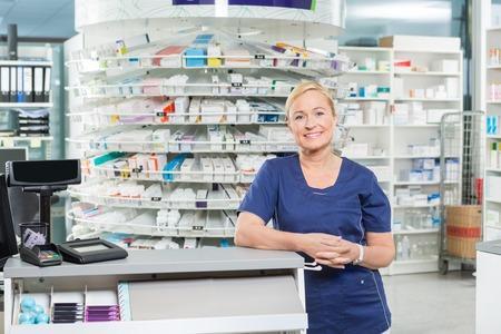 Portret van vertrouwen vrouwelijke apotheker leunend tegen contante balie in de apotheek Stockfoto