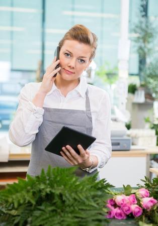mujer con rosas: Retrato de floristería mujer utilizando teléfono móvil y tableta digital en el contador en la tienda de flores