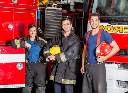 leaning on the truck: Portrait of confident young firefighters standing against trucks at fire station Stock Photo
