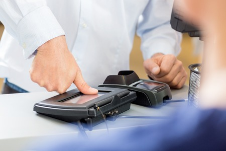 Midsection of customer giving thumb impression to make payment in pharmacy Standard-Bild