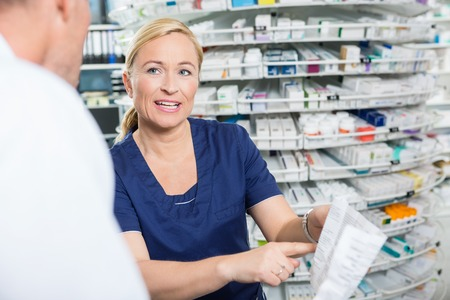 Vrouwelijke apotheker uitleggen de details van het product om mannelijke klant in de farmacie