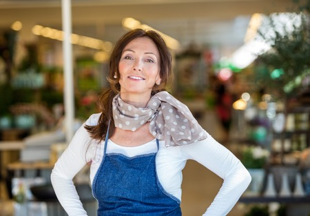 adult woman: Portrait of smiling mid adult woman in flower shop Stock Photo