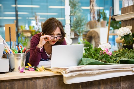 proprietor: Shocked mid adult female florist holding glasses while using laptop at counter in flower shop