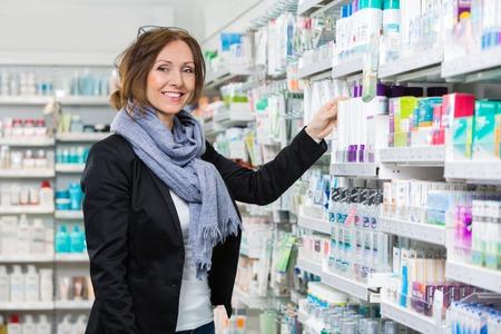 pharmacy: Portrait of smiling female consumer choosing product in pharmacy Stock Photo