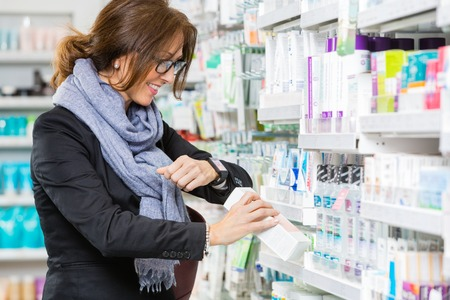 mid adult female: Happy mid adult female customer scanning product through smartwatch in pharmacy