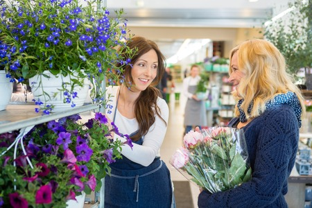 salesgirl: Salesgirl assisting female customer in buying flower at store