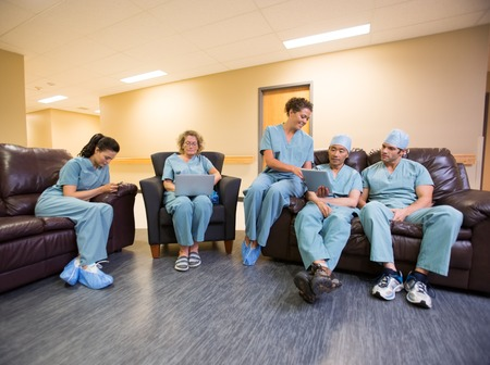 Integrale di chirurghi e infermieri che utilizzano tecnologie nella sala d'attesa dell'ospedale photo