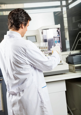 mid adult male: Mid adult male scientist analyzing urine samples in laboratory