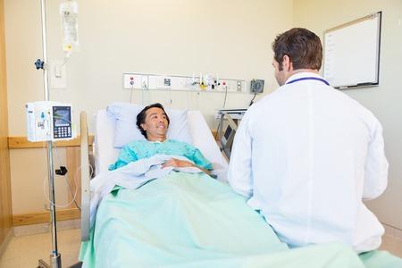 Sorridente paziente matura guardando medico mentre sdraiata sul letto nella stanza d'ospedale photo