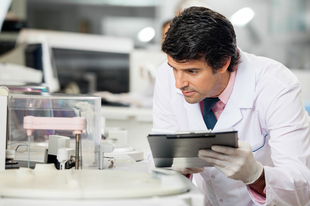 scientist: Male scientist observing experiment in laboratory