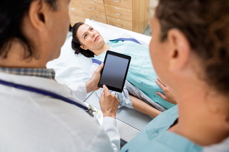 x ray machine: Doctor and nurse using digital tablet while female patient lying on xray table in hospital room Stock Photo