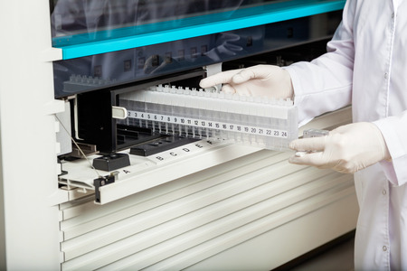 analyzer: Midsection of technician placing samples in analyzer at laboratory