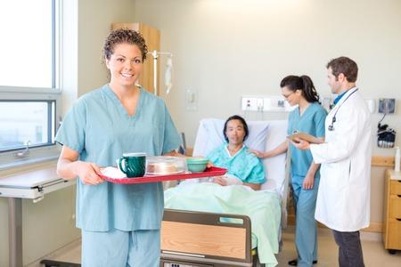 Ritratto di fiducia infermiere vassoio della colazione in possesso con il team medico e paziente in background in ospedale photo