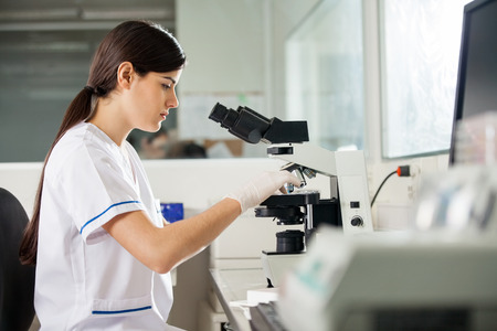 med: Side view of young female scientist using microscope in laboratory Stock Photo