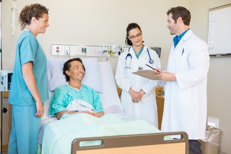patient in hospital: Young doctors discussing notes while happy patient and nurse looking at them in hospital room