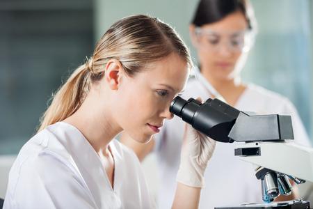 laboratorio clinico: Técnico mujer joven que mira en el microscopio en laboratorio médico Foto de archivo