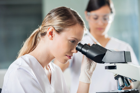medical laboratory: Young female technician looking into microscope in medical laboratory